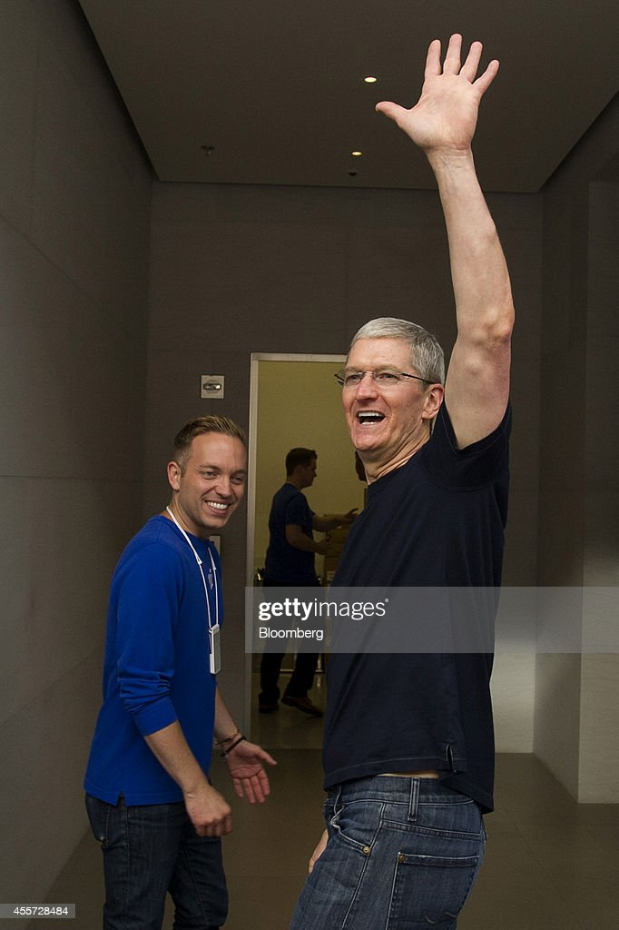 Tim Cook, chief executive officer of Apple Inc., right, waves to customers while leaving the sales launch for the iPhone 6 and iPhone 6 Plus at the Apple Inc. store in Palo Alto, California, U.S., on Friday, Sept. 19, 2014. Apple Inc.'s stores attracted long lines of shoppers for the debut of the latest iPhones, indicating healthy demand for the bigger-screen smartphones. The larger iPhone 6 Plus is already selling out at some stores across the U.S. Photographer: David Paul Morris/Bloomberg via Getty Images