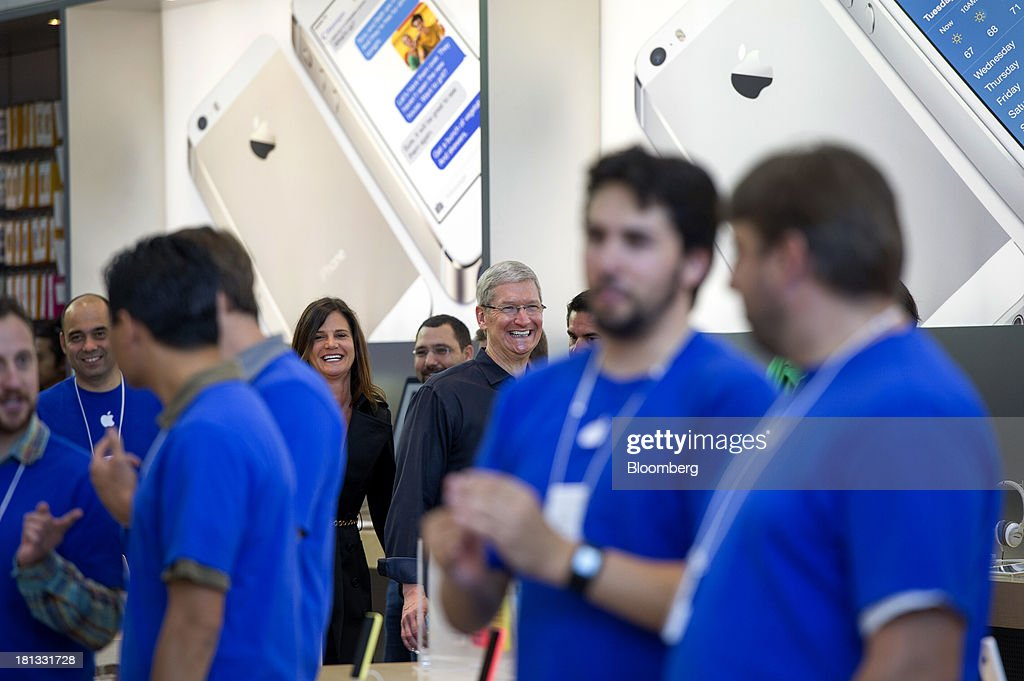 Tim Cook, chief executive officer of Apple Inc., smiles while leaving the launch of the iPhone 5c and 5s at the company's new store in Palo Alto, California, U.S., on Friday, Sept. 20, 2013. Apple Inc. attracted long lines of shoppers at its retail stores today for the global debut of its latest iPhones, in the company's biggest move this year to stoke new growth. Photographer: David Paul Morris/Bloomberg via Getty Images