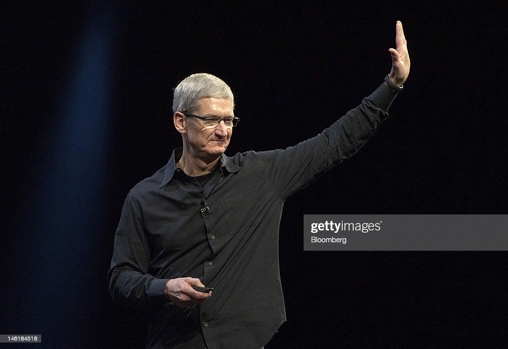 Tim Cook, chief executive officer of Apple Inc., waves to the crowd at the end of his keynote speech at the Apple Worldwide Developers Conference in San Francisco, California, U.S., on Monday, June 11, 2012. Apple Inc. is releasing a fresh lineup of computers and software tools to woo consumers and keep developers making applications amid accelerating rivalry from Google Inc., Microsoft Corp. and, now, Facebook Inc. Photographer: David Paul Morris/Bloomberg via Getty Images