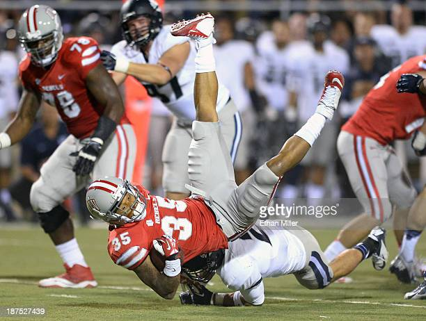 Tim Cornett of the UNLV Rebels is tackled by Brian Suite of the Utah State Aggies during their game at Sam Boyd Stadium on November 9 2013 in Las...