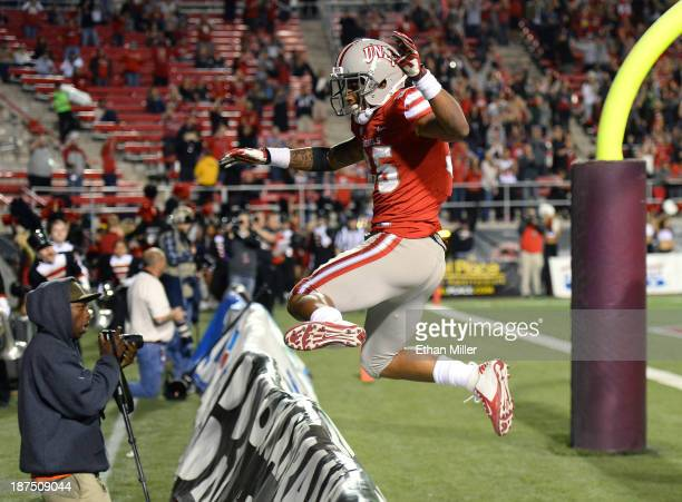 Tim Cornett of the UNLV Rebels leaps over a sideline advertising sign behind the end zone after scoring on a fouryard touchdown run against the Utah...