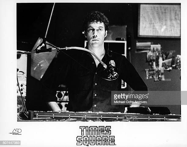 Tim Curry an all night disc jockey stands behind a microphone in a scene from the movie 'Times Square' circa 1980