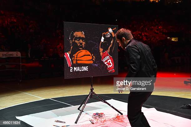 Tim Decker Speed Painter paints portraits of Moses Malone and Darryl Dawkins during halftime of the Philadelphia 76ers against the Utah Jazz at Wells...