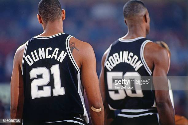 Tim Duncan and David Robinson of the San Antonio Spurs looks on against the Denver Nuggets on October 31 1997 at McNichols Arena in Denver Colorado...