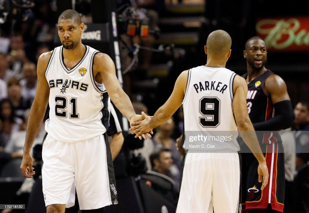 Tim Duncan #21 and Tony Parker #9 of the San Antonio Spurs celebrate as Dwyane Wade #3 of the Miami Heat reacts in the third quarter during Game Five of the 2013 NBA Finals at the AT&T Center on June 16, 2013 in San Antonio, Texas.