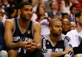Tim Duncan and Tony Parker of the San Antonio Spurs look on from the bench against the Miami Heat during Game Four of the 2014 NBA Finals at American...