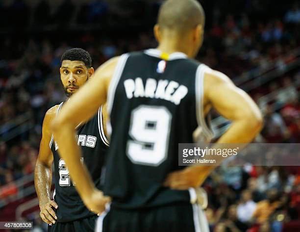 Tim Duncan and Tony Parker of the San Antonio Spurs wait on the court during their preseason game against the Houston Rockets at Toyota Center on...