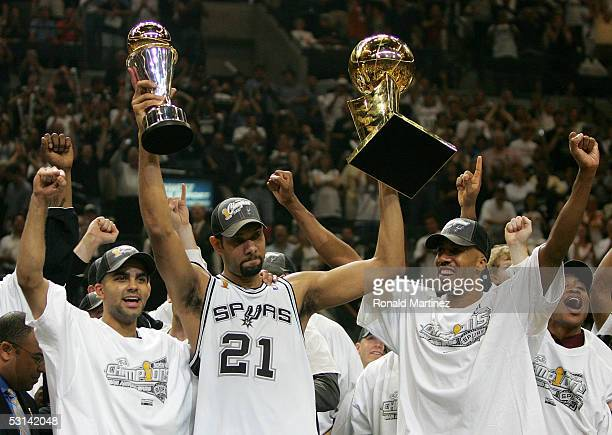 Tim Duncan center holds up the Finals MVP trophy and the Larry O'Brien trophy as teammates Tony Parker left and Bruce Bowen of the San Antonio Spurs...