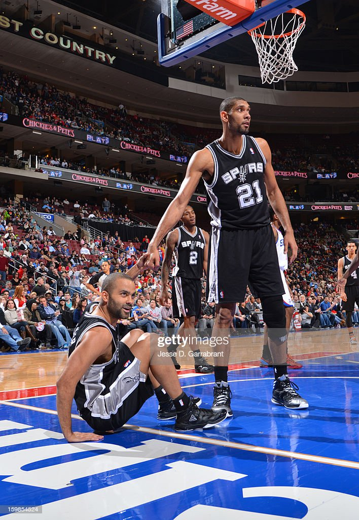 Tim Duncan #21 helps up Tony Parker #9 of the San Antonio Spurs during the game against the Philadelphia 76ers at the Wells Fargo Center on January 21, 2013 in Philadelphia, Pennsylvania.