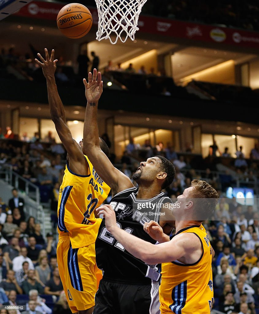 Tim Duncan (C) of San Antonio is challenged by Leon Radosevic (L) and Alex Renfroe (R) of Berlin during the NBA Global Games Tour 2014 match between Alba Berlin and San Antonio Spurs at O2 World on October 8, 2014 in Berlin, Germany.