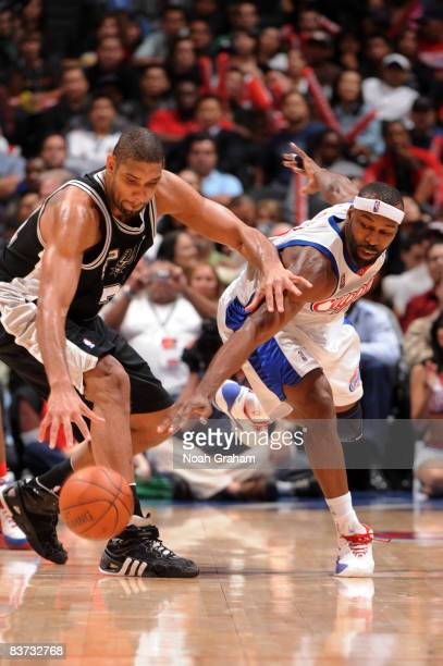 Tim Duncan of the San Antonio Spurs and Baron Davis of the Los Angeles Clippers reach for a loose ball during their game at Staples Center on...