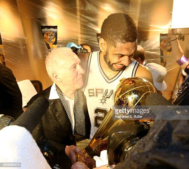Tim Duncan of the San Antonio Spurs and Head Coach Gregg Popovich showered with champagne in the locker room with the Larry O'Brien Trophy after...