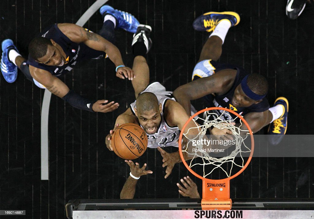 <a gi-track='captionPersonalityLinkClicked' href=/galleries/search?phrase=Tim+Duncan&family=editorial&specificpeople=201467 ng-click='$event.stopPropagation()'>Tim Duncan</a> #21 of the San Antonio Spurs attempts a shot against Mike Conley #11 and <a gi-track='captionPersonalityLinkClicked' href=/galleries/search?phrase=Zach+Randolph&family=editorial&specificpeople=201595 ng-click='$event.stopPropagation()'>Zach Randolph</a> #50 of the Memphis Grizzlies during Game Two of the Western Conference Finals of the 2013 NBA Playoffs at AT&T Center on May 21, 2013 in San Antonio, Texas.