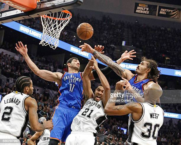 Tim Duncan of the San Antonio Spurs battles Enes Kanter and Steven Adams of the Oklahoma City Thunder for a rebound in game Five of the Western...