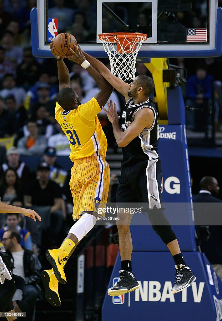 Tim Duncan #21 of the San Antonio Spurs blocks a shot by Festus Ezeli #31 of the Golden State Warriors at Oracle Arena on February 22, 2013 in Oakland, California. The Warriors are wearing new short-sleeved uniforms for the first time. The Warriors won the game in overtime.