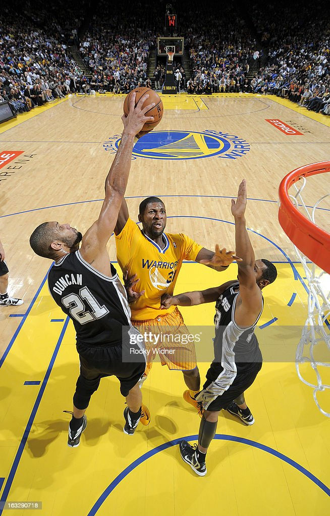 Tim Duncan #21 of the San Antonio Spurs blocks the shot of Festus Ezeli #31 of the Golden State Warriors on February 22, 2013 at Oracle Arena in Oakland, California.