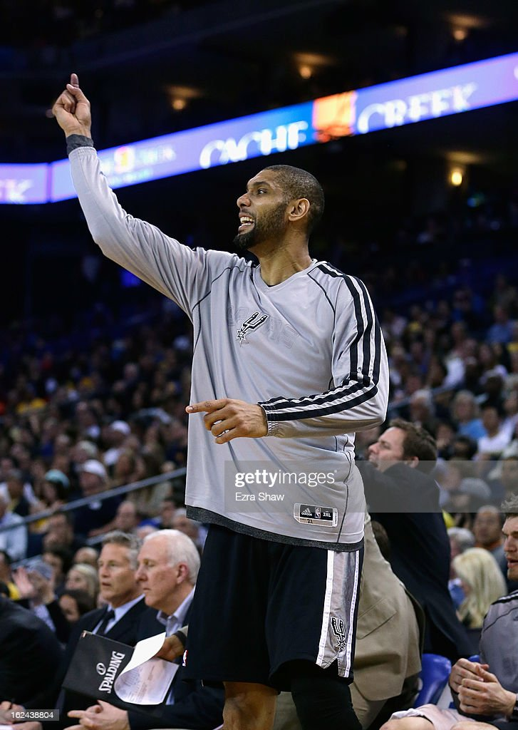 Tim Duncan #21 of the San Antonio Spurs cheers on his team from the bench during their game against the Golden State Warriors at Oracle Arena on February 22, 2013 in Oakland, California. The Warriors are wearing new short-sleeved uniforms for the first time. The Warriors won the game in overtime.