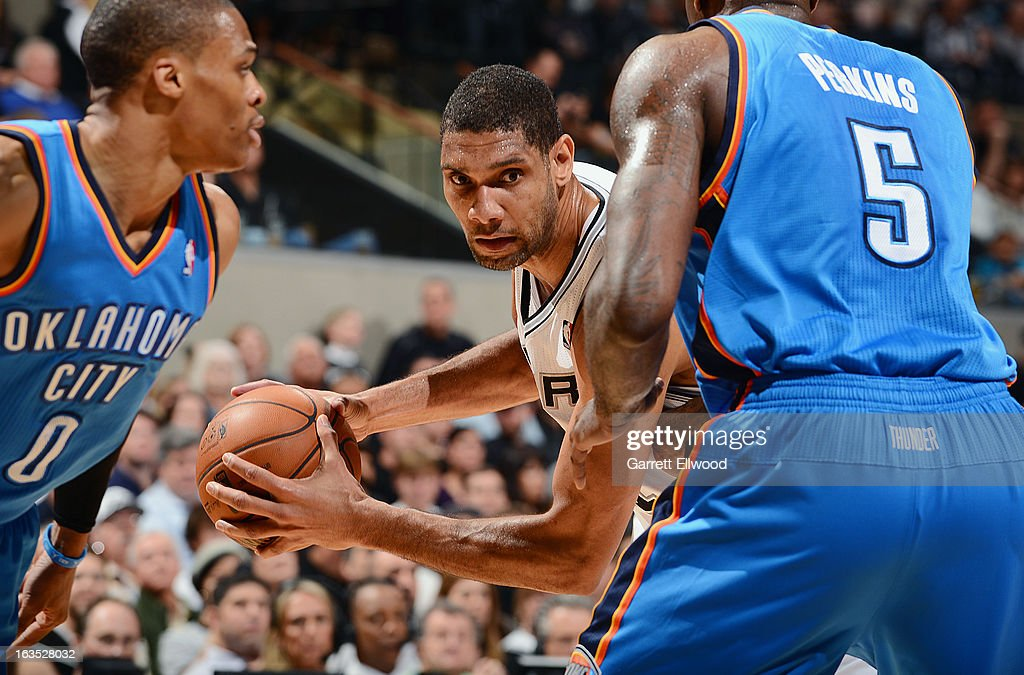 Tim Duncan #21 of the San Antonio Spurs controls the ball against Kendrick Perkins #5 of the Oklahoma City Thunder on March 11, 2013 at the AT&T Center in San Antonio, Texas.
