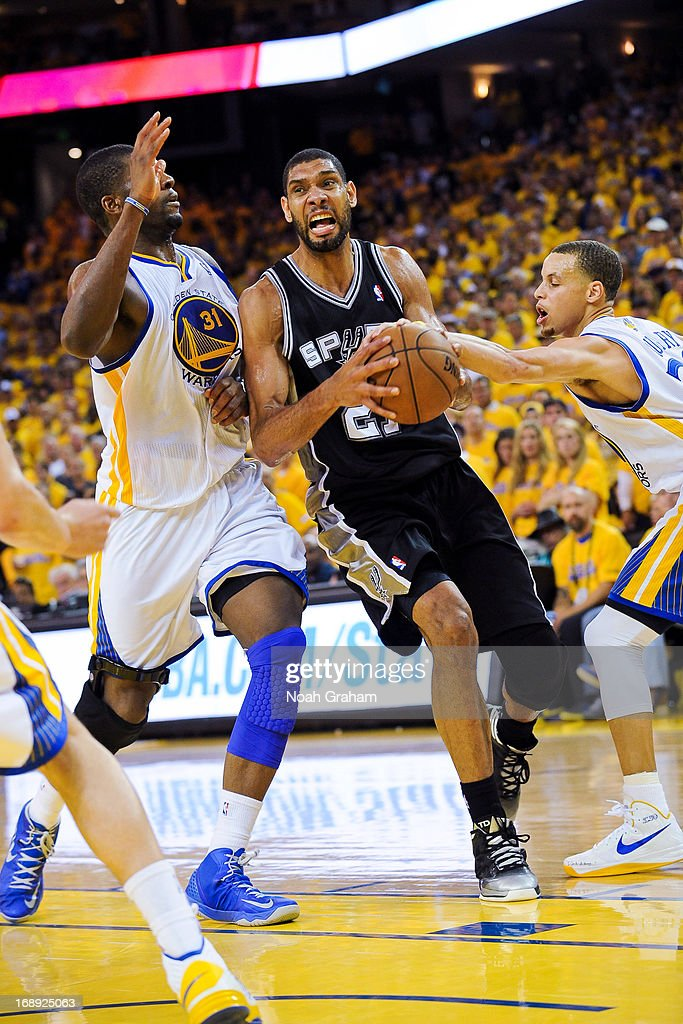 Tim Duncan #21 of the San Antonio Spurs drives against Festus Ezeli #31 and Stephen Curry #30 of the Golden State Warriors in Game Six of the Western Conference Semifinals during the 2013 NBA Playoffs on May 16, 2013 at Oracle Arena in Oakland, California.