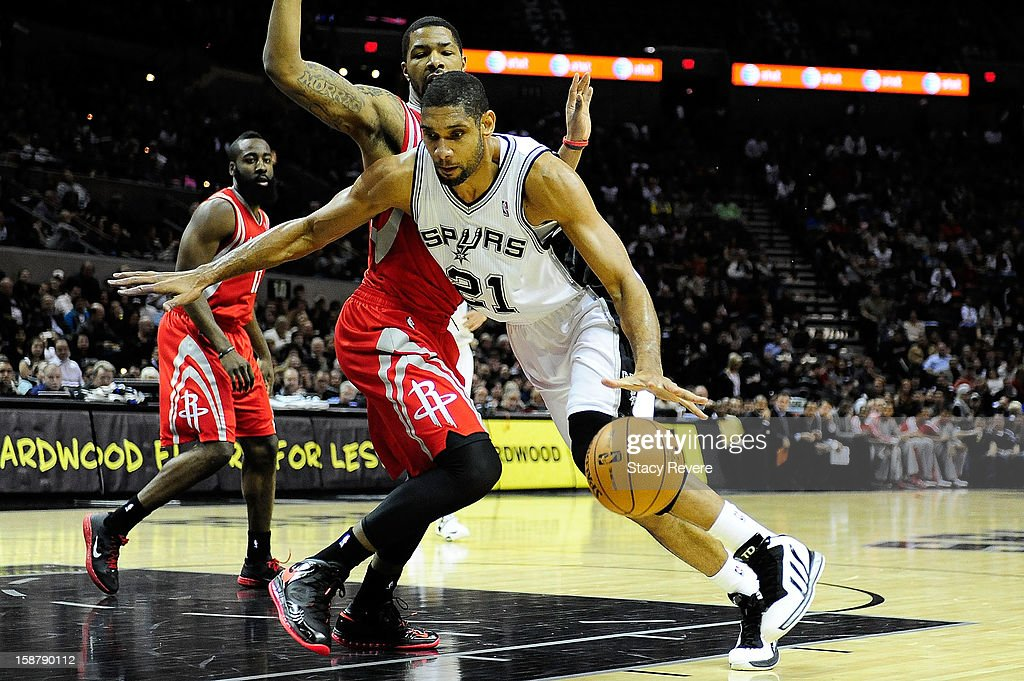Tim Duncan #21 of the San Antonio Spurs drives around Marcus Morris #2 of the Houston Rockets during a game at AT&T Center on December 28, 2012 in San Antonio, Texas.