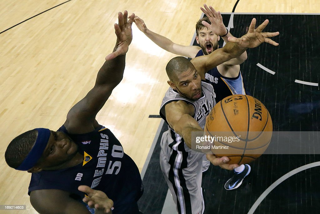 <a gi-track='captionPersonalityLinkClicked' href=/galleries/search?phrase=Tim+Duncan&family=editorial&specificpeople=201467 ng-click='$event.stopPropagation()'>Tim Duncan</a> #21 of the San Antonio Spurs drives for a shot attempt in th esecond half between <a gi-track='captionPersonalityLinkClicked' href=/galleries/search?phrase=Zach+Randolph&family=editorial&specificpeople=201595 ng-click='$event.stopPropagation()'>Zach Randolph</a> (L) #50 and <a gi-track='captionPersonalityLinkClicked' href=/galleries/search?phrase=Marc+Gasol&family=editorial&specificpeople=661205 ng-click='$event.stopPropagation()'>Marc Gasol</a> #33 of the Memphis Grizzlies during Game Two of the Western Conference Finals of the 2013 NBA Playoffs at AT&T Center on May 21, 2013 in San Antonio, Texas.