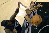 Tim Duncan of the San Antonio Spurs drives for a shot attempt in th esecond half between Zach Randolph and Marc Gasol of the Memphis Grizzlies during...