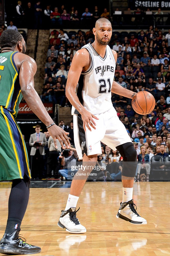 Tim Duncan #21 of the San Antonio Spurs drives to the basket against Al Jefferson #25 of the Utah Jazz on March 22, 2013 at the AT&T Center in San Antonio, Texas.
