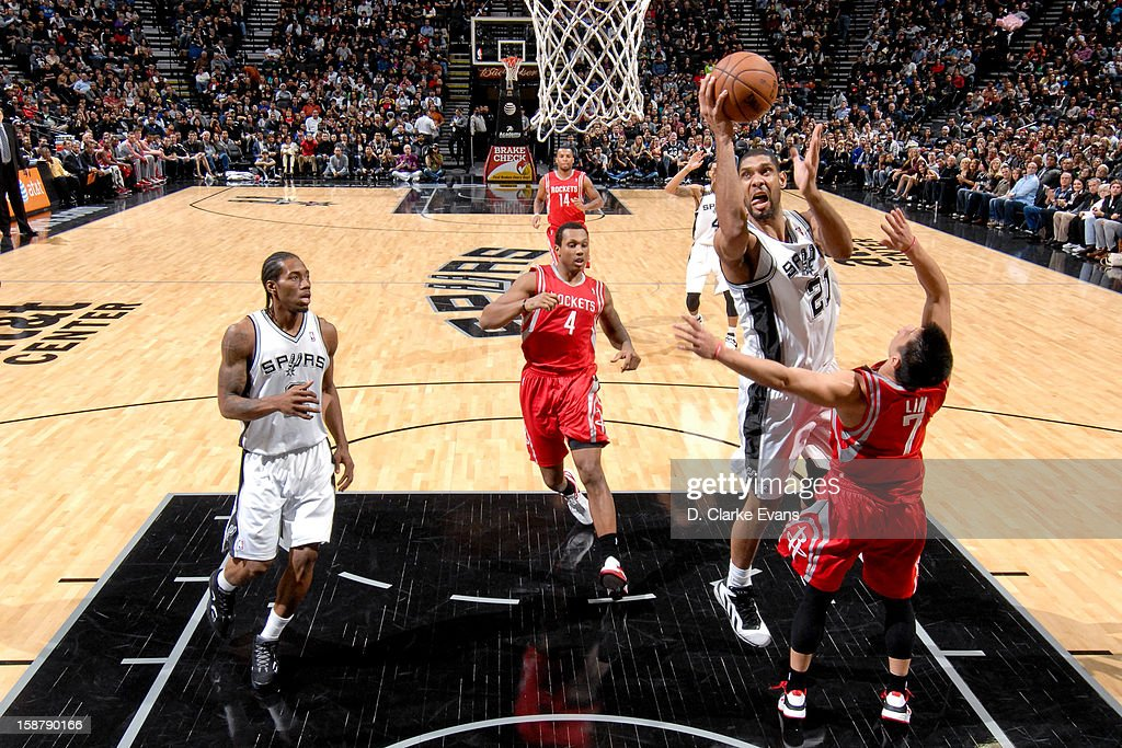 Tim Duncan #21 of the San Antonio Spurs drives to the basket against Jeremy Lin #7 of the Houston Rockets on December 28, 2012 at the AT&T Center in San Antonio, Texas.