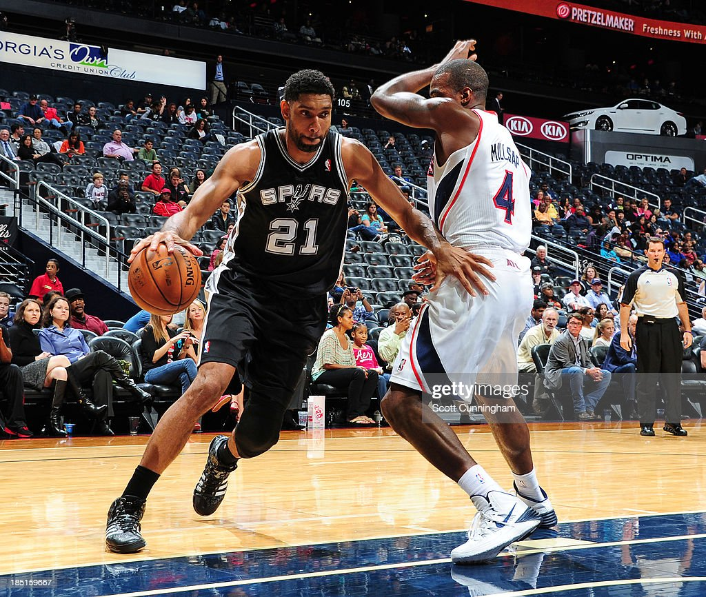 <a gi-track='captionPersonalityLinkClicked' href=/galleries/search?phrase=Tim+Duncan&family=editorial&specificpeople=201467 ng-click='$event.stopPropagation()'>Tim Duncan</a> #21 of the San Antonio Spurs drives to the basket against <a gi-track='captionPersonalityLinkClicked' href=/galleries/search?phrase=Paul+Millsap&family=editorial&specificpeople=880017 ng-click='$event.stopPropagation()'>Paul Millsap</a> #4 of the Atlanta Hawks on October 17, 2013 at Philips Arena in Atlanta, Georgia.