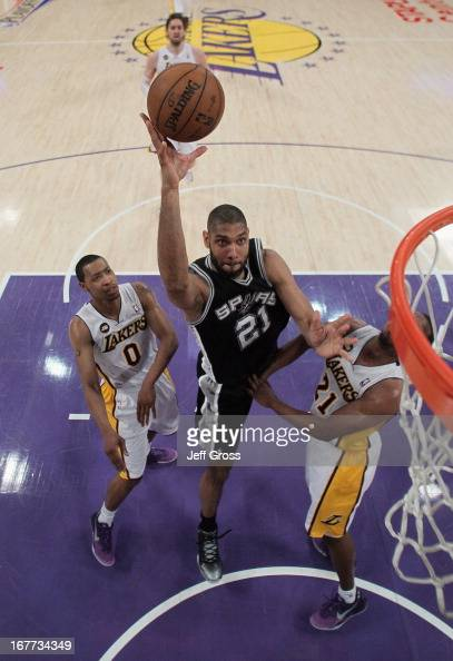 Tim Duncan of the San Antonio Spurs drives to the basket between Andrew Goudelock and Chris Duhon of the Los Angeles Lakers in the first half during...