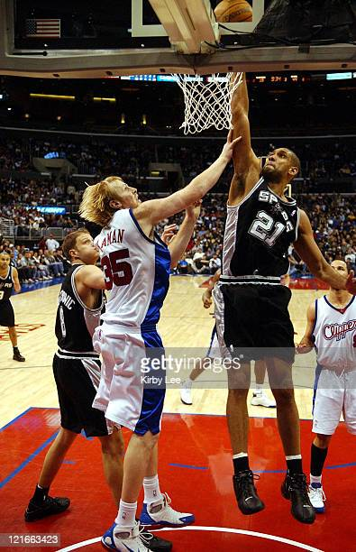 Tim Duncan of the San Antonio Spurs dunks over Chris Kaman of the Los Angeles Clippers during 9879 victory at the Staples Center in Los Angeles Calif...