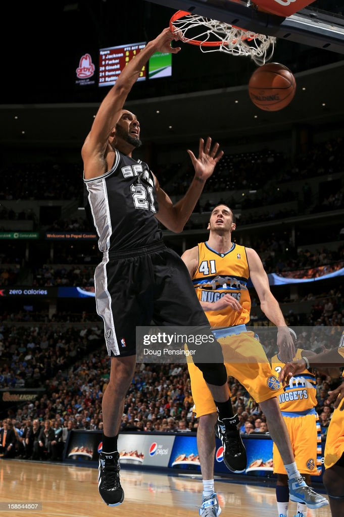 <a gi-track='captionPersonalityLinkClicked' href=/galleries/search?phrase=Tim+Duncan&family=editorial&specificpeople=201467 ng-click='$event.stopPropagation()'>Tim Duncan</a> #21 of the San Antonio Spurs dunks the ball against <a gi-track='captionPersonalityLinkClicked' href=/galleries/search?phrase=Kosta+Koufos&family=editorial&specificpeople=4216032 ng-click='$event.stopPropagation()'>Kosta Koufos</a> #41 of the Denver Nuggetsat the Pepsi Center on December 18, 2012 in Denver, Colorado. The Nuggets defeated the Spurs 112-106.