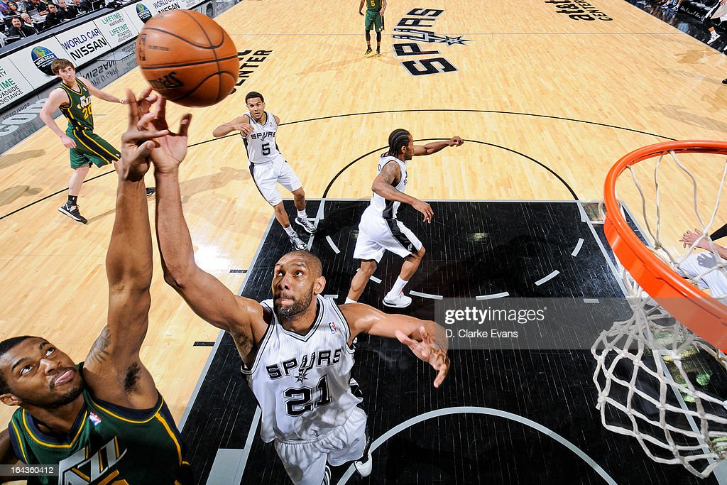 Tim Duncan #21 of the San Antonio Spurs fights for a rebound against Derrick Favors #15 of the Utah Jazz on March 22, 2013 at the AT&T Center in San Antonio, Texas. Duncan's 16 rebounds in the game secured 13th place for him on the NBA all-time career rebounding list.