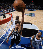 Tim Duncan of the San Antonio Spurs goes in for a layup past Kevin Garnett of the Minnesota Timberwolves during a game at Target Center on March 23...