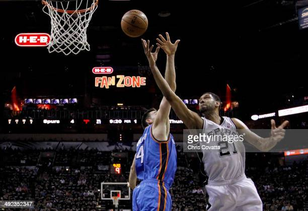 Tim Duncan of the San Antonio Spurs goes up for a shot against Nick Collison of the Oklahoma City Thunder in the first half in Game One of the...