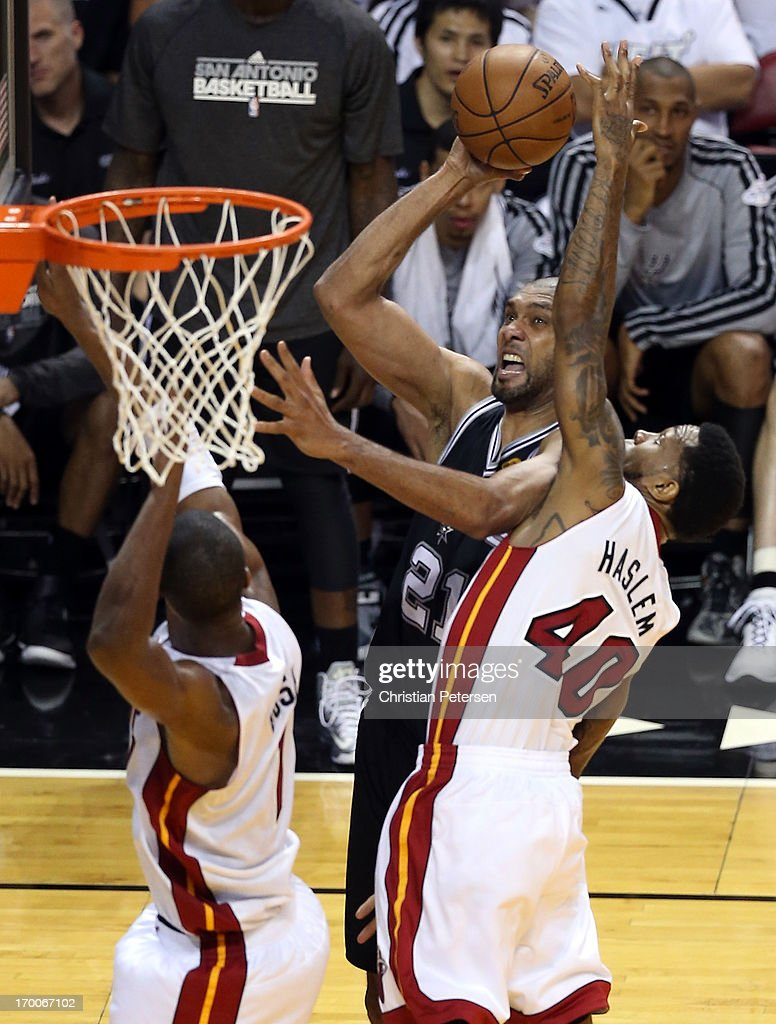 Tim Duncan #21 of the San Antonio Spurs goes up for a shot against Udonis Haslem #40 and Chris Bosh #1 of the Miami Heat in the third quarter during Game One of the 2013 NBA Finals at AmericanAirlines Arena on June 6, 2013 in Miami, Florida.