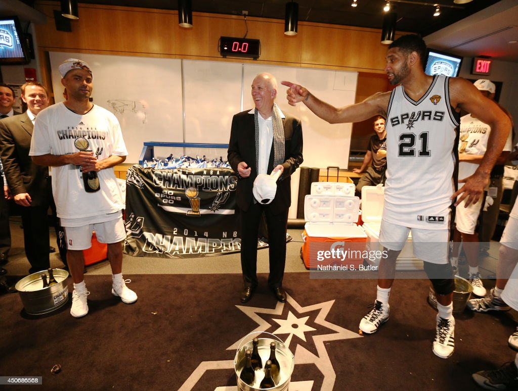 <a gi-track='captionPersonalityLinkClicked' href=/galleries/search?phrase=Tim+Duncan&family=editorial&specificpeople=201467 ng-click='$event.stopPropagation()'>Tim Duncan</a> #21 of the San Antonio Spurs, Head Coach <a gi-track='captionPersonalityLinkClicked' href=/galleries/search?phrase=Gregg+Popovich&family=editorial&specificpeople=202904 ng-click='$event.stopPropagation()'>Gregg Popovich</a> and Tony Parker react in the locker room after winning the 2014 NBA Finals at AT&T Center on June 15, 2014 in San Antonio, Texas.