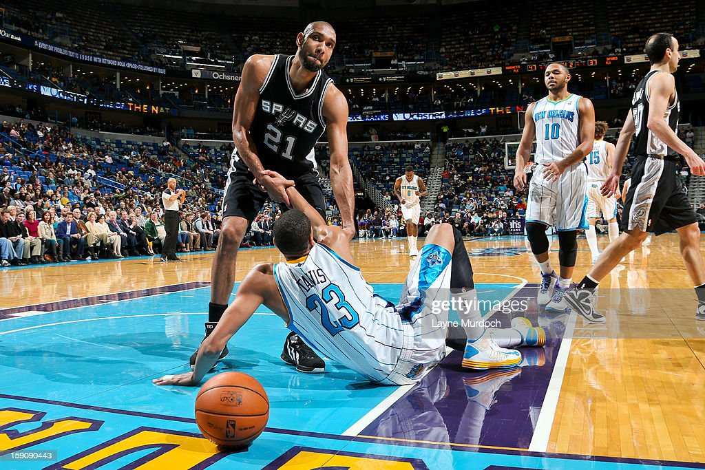 Tim Duncan #21 of the San Antonio Spurs helps up Anthony Davis #23 of the New Orleans Hornets during their game on January 7, 2013 at the New Orleans Arena in New Orleans, Louisiana.