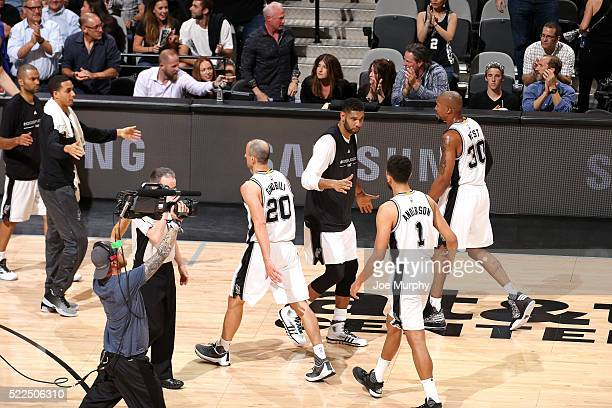 Tim Duncan of the San Antonio Spurs high fives his teammates Kyle Anderson and David West of the San Antonio Spurs during the game against the...