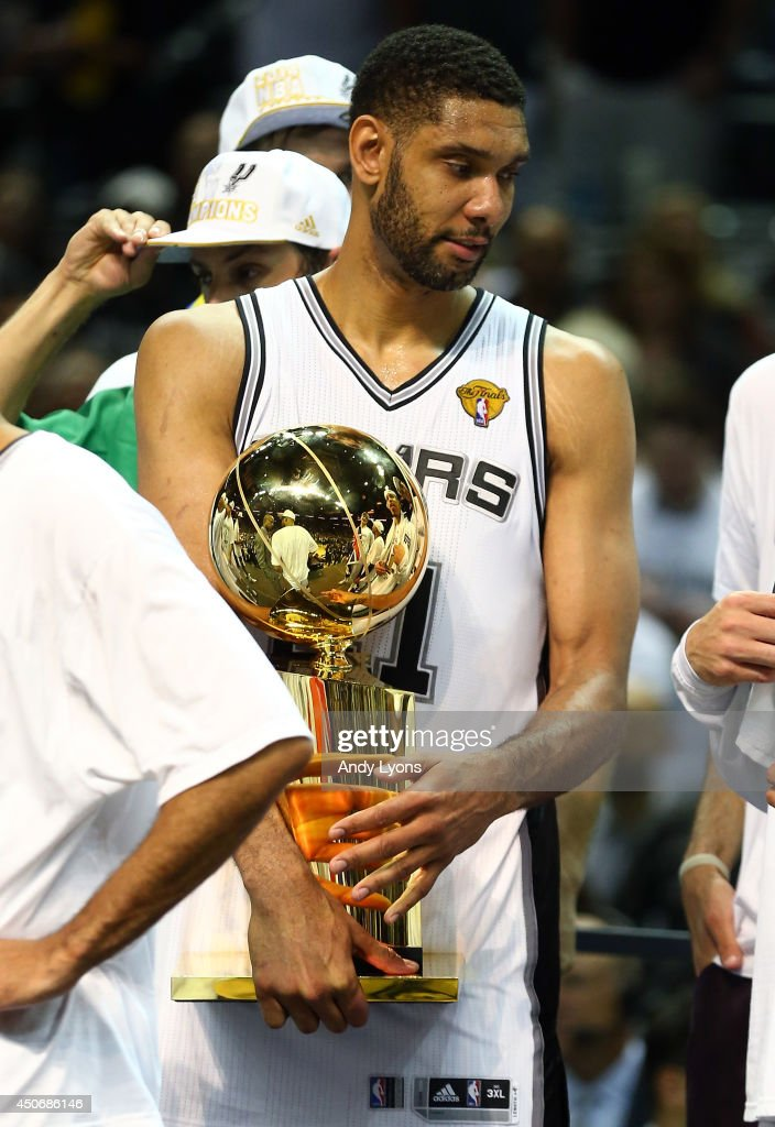 <a gi-track='captionPersonalityLinkClicked' href=/galleries/search?phrase=Tim+Duncan&family=editorial&specificpeople=201467 ng-click='$event.stopPropagation()'>Tim Duncan</a> #21 of the San Antonio Spurs holds the Larry O'Brien trophy on the fourt after defeating the Miami Heat in Game Five of the 2014 NBA Finals at the AT&T Center on June 15, 2014 in San Antonio, Texas.
