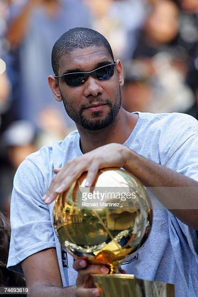 Tim Duncan of the San Antonio Spurs holds the Larry O'Brien trophy during the NBA championship parade down the San Antonio River walk June 17 2007 in...