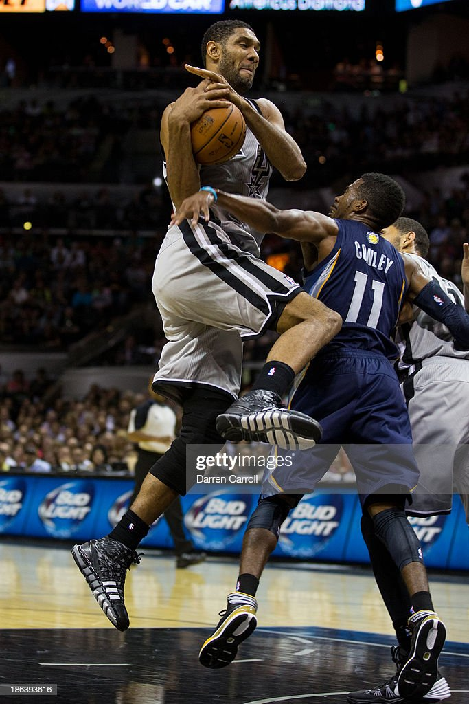 Tim Duncan #21 of the San Antonio Spurs is fouled by Mike Conley #11 of the Memphis Grizzlies during a game on October 30, 2013 at the AT&T Center in San Antonio, Texas.