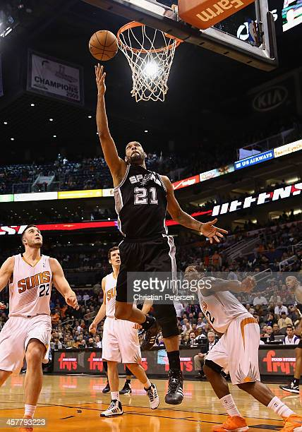Tim Duncan of the San Antonio Spurs lays up a shot ahead of Miles Plumlee Goran Dragic and Eric Bledsoe of the Phoenix Suns during the second half of...