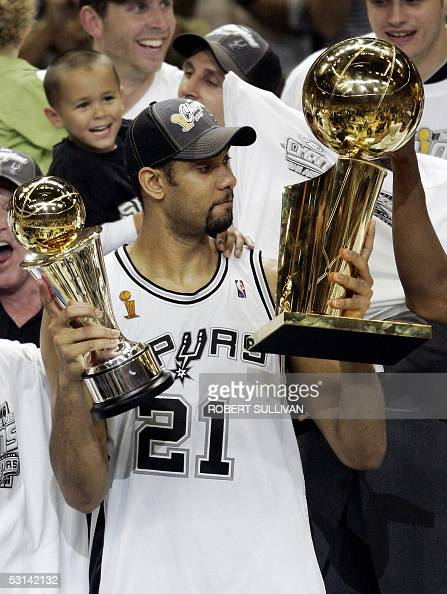 Tim Duncan of the San Antonio Spurs looks at the championship trophy while holding his MVP trophy after his team's victory over the Detroit Pistons...