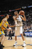 Tim Duncan of the San Antonio Spurs looks to move the ball against Tyson Chandler of the New Orleans Hornets in Game Six of the Western Conference...