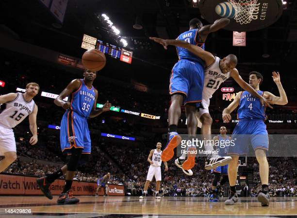 Tim Duncan of the San Antonio Spurs looses the ball as he goes up for a shot against Serge Ibaka and Nick Collison of the Oklahoma City Thunder in...