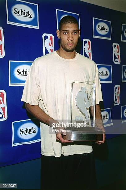 Tim Duncan of the San Antonio Spurs poses for a portrait after receiving the Rookie of the Year Trophy on April 27 1998 in San Antonio Texas NOTE TO...