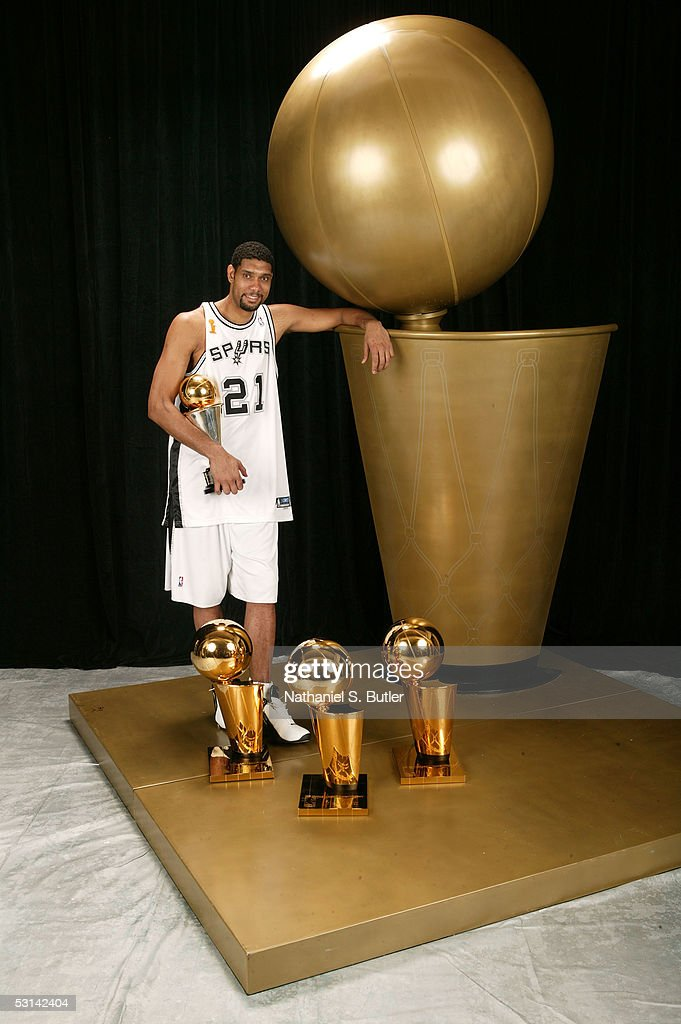 Tim Duncan of the San Antonio Spurs poses with the Spurs 3 world championship trophies and his 2005 Finals MVP trophy following Game Seven of the...
