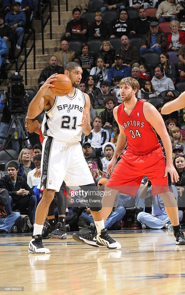 Tim Duncan #21 of the San Antonio Spurs protects the ball from Aaron Gray #34 of the Toronto Raptors during the game between the Toronto Raptors and the San Antonio Spurs on December 26, 2012 at the AT&T Center in San Antonio, Texas.