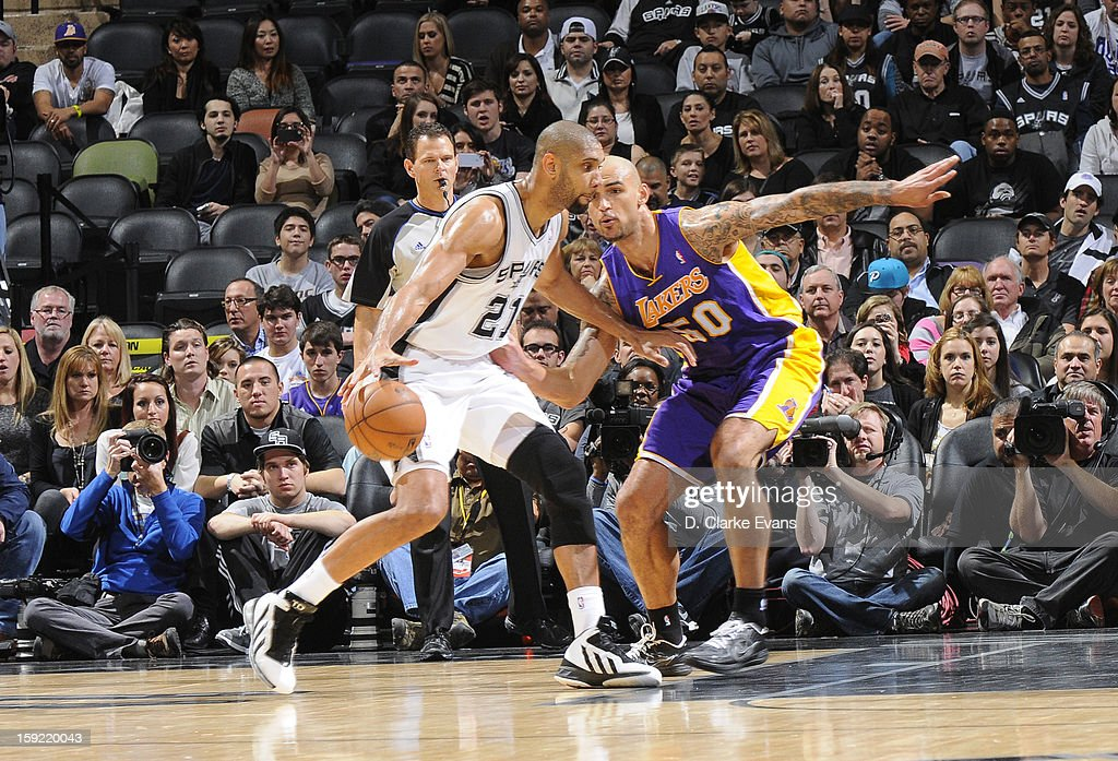 Tim Duncan #21 of the San Antonio Spurs protects the ball from Robert Sacre #50 of the Los Angeles Lakers during the game between the Los Angeles Lakers and the San Antonio Spurs on January 9, 2013 at the AT&T Center in San Antonio, Texas.